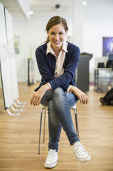 Full length portrait of confident businesswoman sitting on chair in office - MASF04996