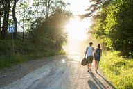 Full length rear view of couple walking on dirt road - MASF05017