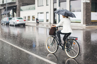 Full length rear view of businesswoman riding bicycle on wet city street during rainy season - MASF05020