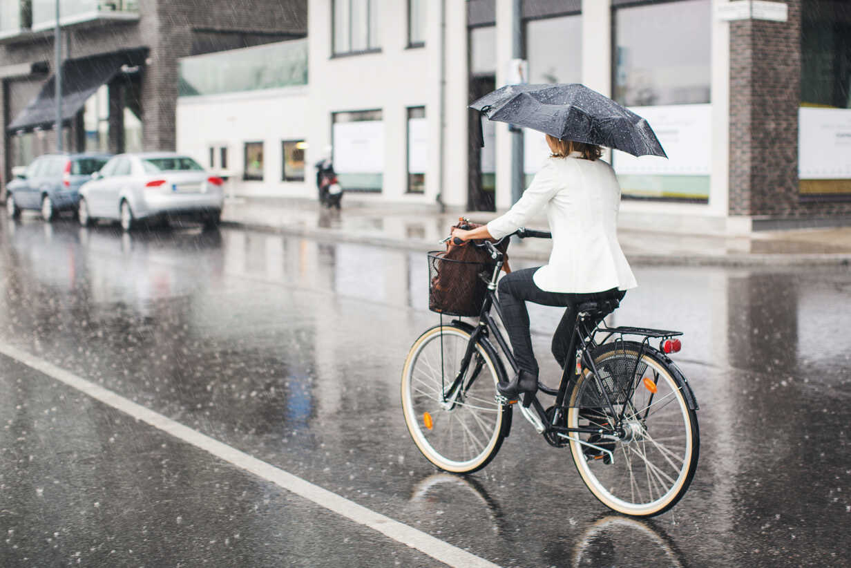 Full length rear view of businesswoman riding bicycle on wet city street during rainy season - MASF05020 - Maskot ./Westend61
