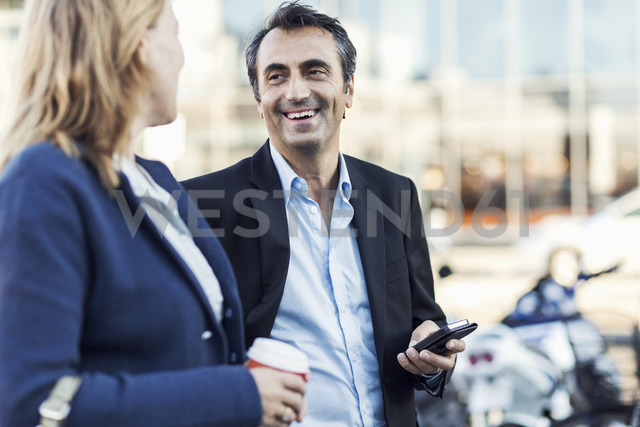 Happy businessman talking to female colleague outdoors - MASF05023 - Maskot ./Westend61