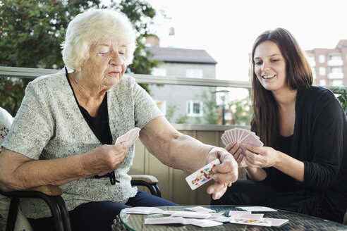 Grandmother and granddaughter playing cards on porch - MASF05029
