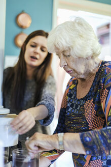 Grandmother and granddaughter preparing coffee at home - MASF05032