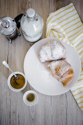 Italian cornettos with powdered sugar on plate, French press - GIOF03914