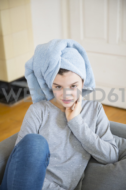 Portrait of girl wearing towel turban sitting on couch at home - LVF06883