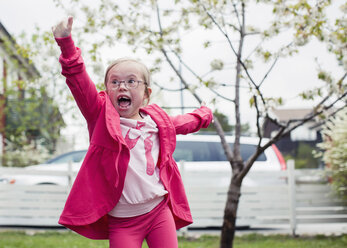 Excited girl with arms outstretched enjoying in lawn - MASF05048