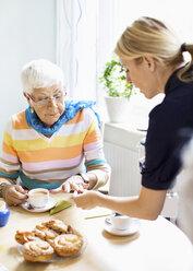 Female caretaker examining senior woman's finger at breakfast table in nursing home - MASF05063