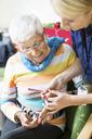 Female caretaker filing senior woman's fingernails at nursing home - MASF05066