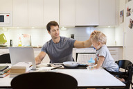 Father stroking baby boy while using laptop at dining table - MASF05078