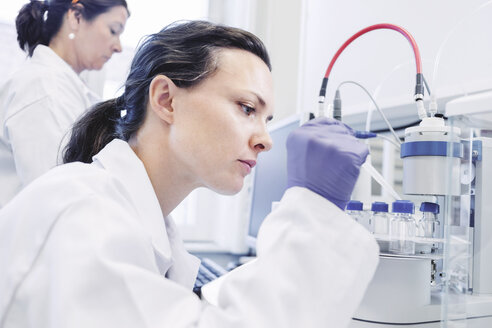 Female scientist using pipette in laboratory - MASF05084