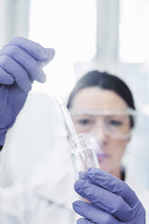 Female scientist examining chemical in laboratory - MASF05087