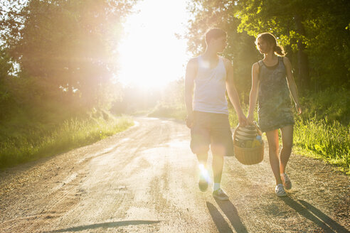 Full length front view of couple walking on dirt road against bright sun - MASF05099
