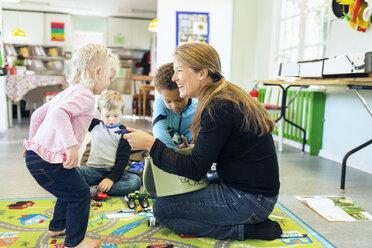 Full length of teacher giving toys to children - MASF05108