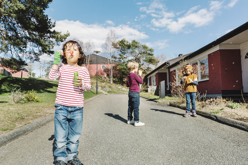 Friends playing with bubble wands on footpath at yard - MASF05120