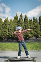 Full length of boy posing while standing on skateboard at yard - MASF05123