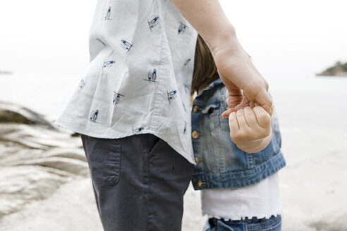 Brother and little sister holding hands on the beach, partial view - KMKF00162