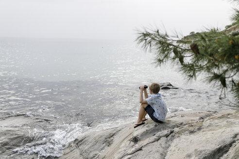 Greece, Chalkidiki, boy with binoculars sitting on rock looking at the sea - KMKF00168