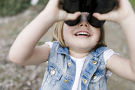 Happy little girl using binoculars - KMKF00171