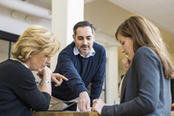 Businessman planning strategy with female colleagues at desk in office meeting - MASF05126