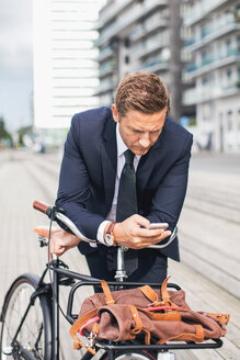 Businessman using smart phone in city while leaning on bicycle - MASF05138