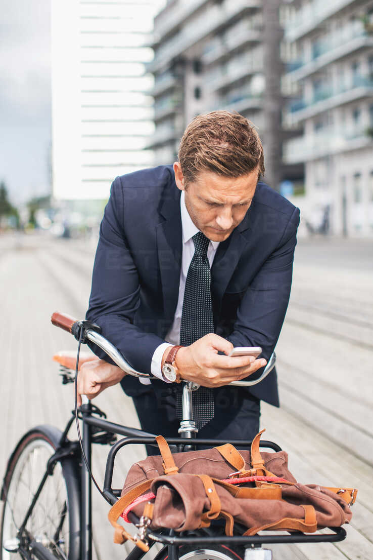 Businessman using smart phone in city while leaning on bicycle - MASF05138 - Maskot ./Westend61