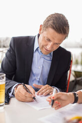 Businessman signing paperwork at outdoor cafe against clear sky - MASF05141