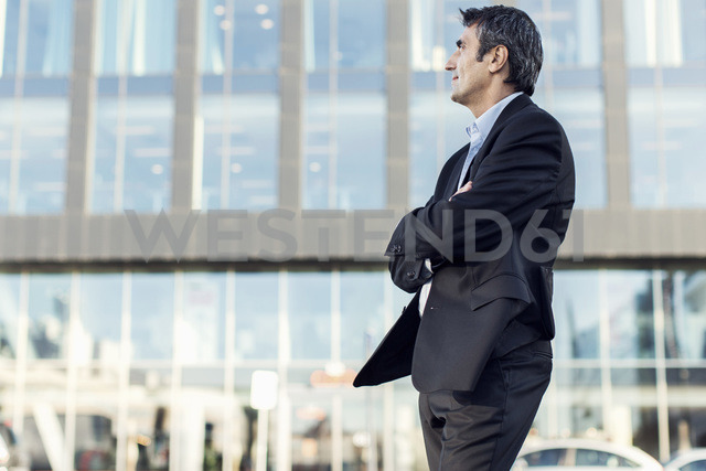 Businessman with arms crossed looking away outside office building - MASF05147