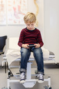 Boy using smart phone on examination table in orthopedic clinic - MASF05150