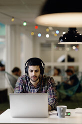 Businessman listening music while working late on laptop in creative office - MASF05162