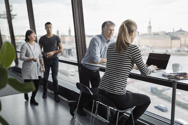 Business people discussing by window in office - MASF05174
