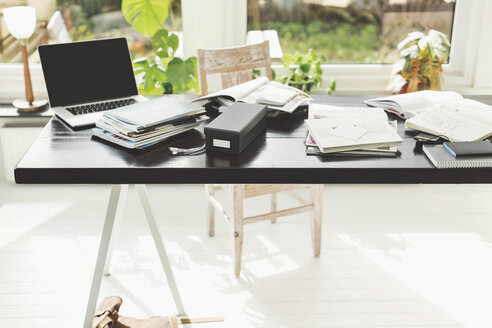 Books and laptop on table in home office - MASF05180