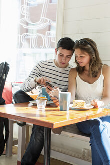 Couple using mobile phones while sitting at restaurant table - MASF05198