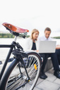 Cropped image of bicycle on sidewalk with business people working on laptop against clear sky - MASF05201