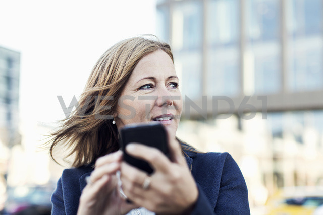 Businesswoman looking away while using mobile phone outdoors - MASF05204