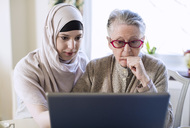 Senior woman and female home caregiver using laptop at home - MASF05237