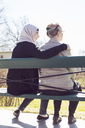 Rear view of senior woman and female home caregiver sitting together on park bench - MASF05240
