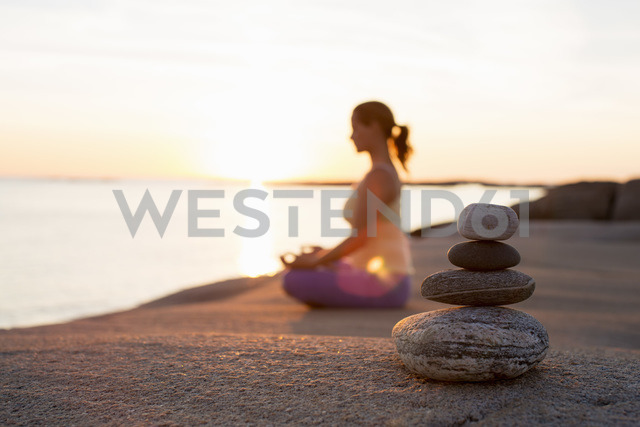 Side view of woman sitting in lotus position on lakeshore with focus on stack of stones - MASF05276 - Kentaroo Tryman/Westend61