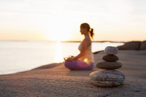 Side view of woman sitting in lotus position on lakeshore with focus on stack of stones - MASF05276