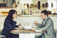 Side view of businessman with female colleague discussing paperwork at restaurant table - MASF05300