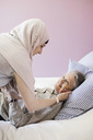 Young female home caregiver assisting senior woman in bed - MASF05318