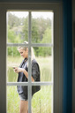 View of woman using mobile phone through closed door - MASF05324