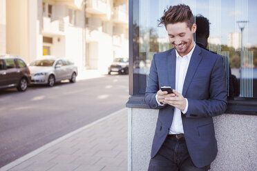 Young businessman using mobile phone against wall by sidewalk - MASF05330