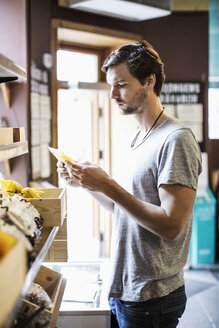 Young man reading label in grocery store - MASF05336