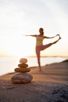 Woman practices yoga on lakeshore with focus on pile of stones - MASF05345