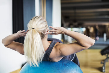 Young woman exercising on fitness ball at gym - MASF05348