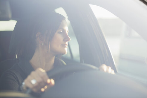 Young businesswoman looking through window while driving car - MASF05351