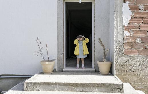 Little girl standing at house entrace using binoculars - KMKF00173
