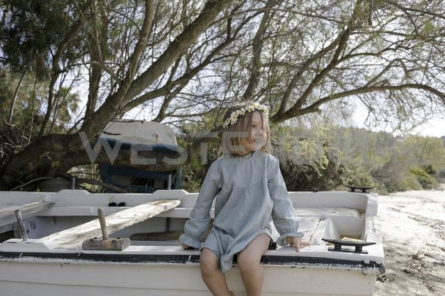 Smiling little girl wearing flowers sitting on boat on the beach - KMKF00179