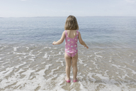 Back view of little girl standing at seafront - KMKF00182