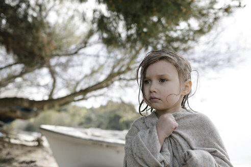 Portrait of sad little girl wrapped in oversized cardigan standing on the beach - KMKF00188